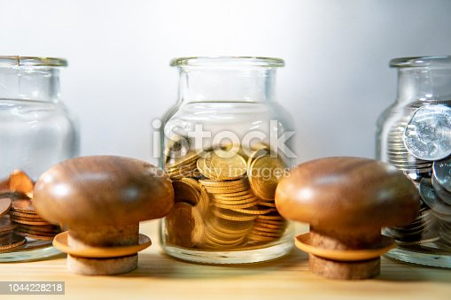 istock Coins in currency glass jars on wooden table. Saving money for future retirement. Financial business investment concept 1044228218