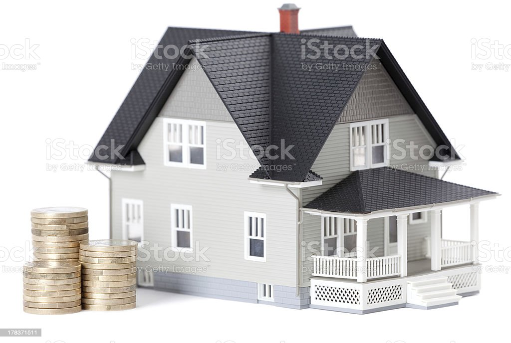 Coins in front of home architectural model royalty-free stock photo