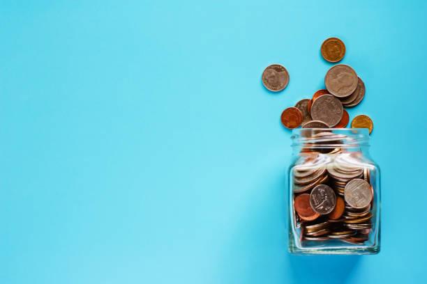 硬幣在玻璃罐子和外面, 泰國貨幣金錢在藍色背景為商業和財務概念 - 硬幣 個照片及圖片檔