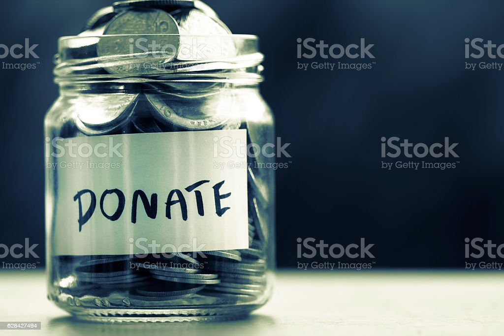 Coins in glass jar for giving and donation concept stock photo