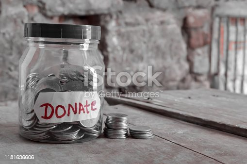 istock Coins in jar and written donate , money on wooden table 1181636606