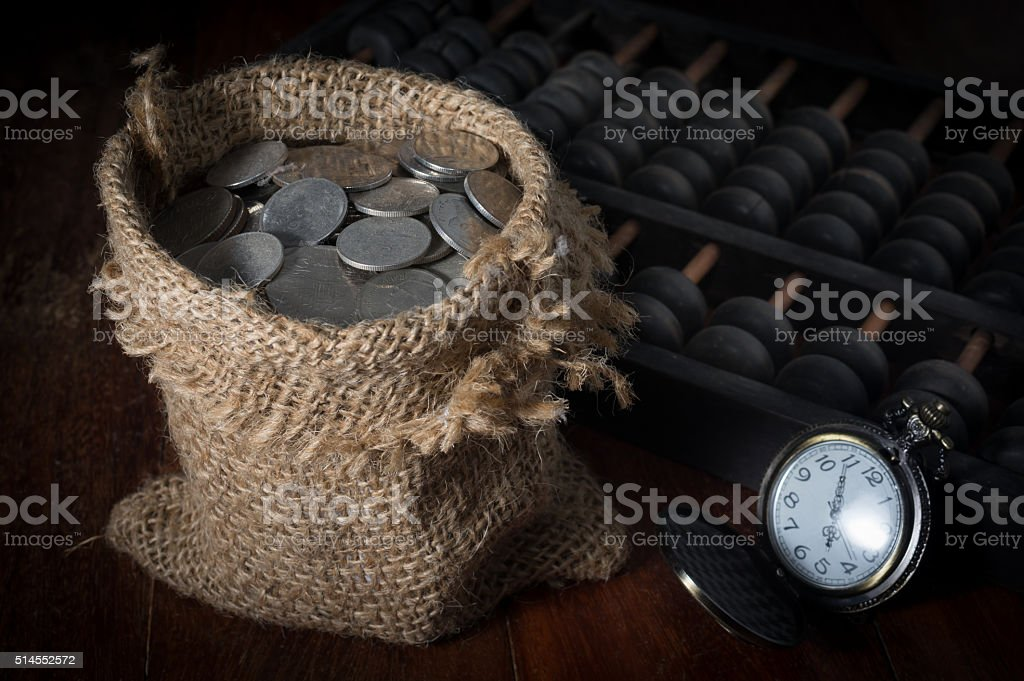 Coins in sack with pocket watch and abacus. stock photo