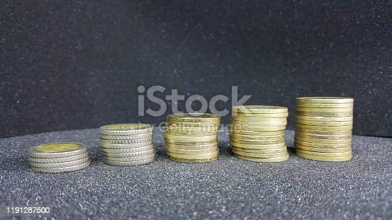 657417590 istock photo coins lined up in a row on the table 1191287500