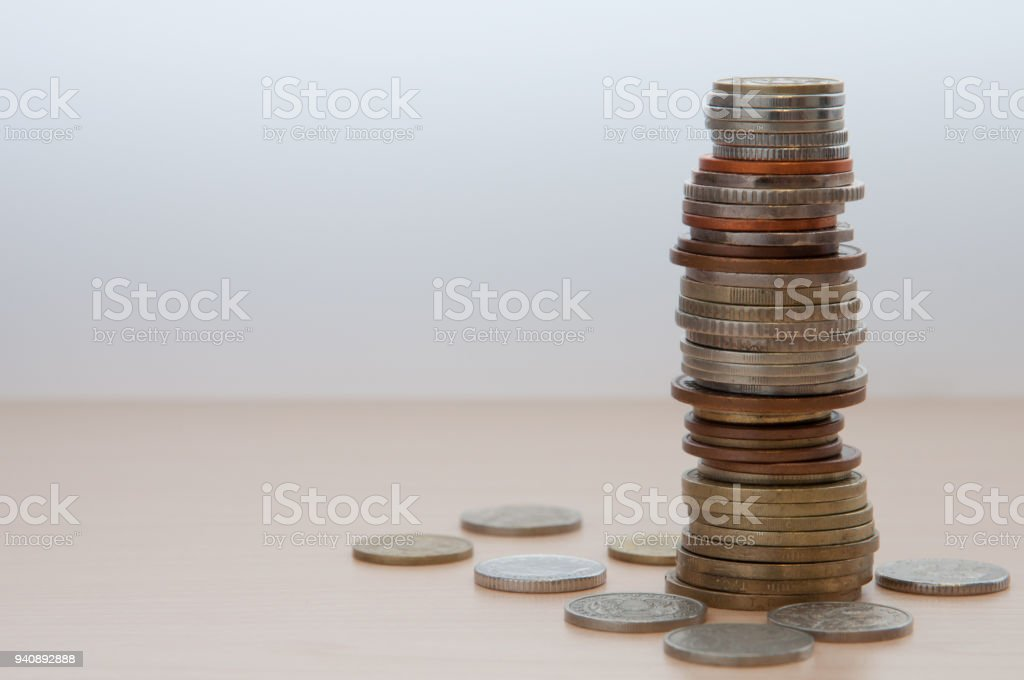 Coins of different countries and different advantages and colors on the wooden table. stock photo
