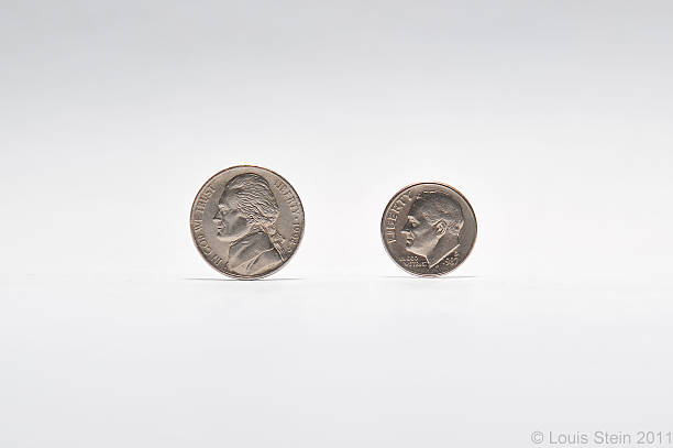 Coins on gray background US Nickel and Dime coins on a gray background  nickel stock pictures, royalty-free photos & images