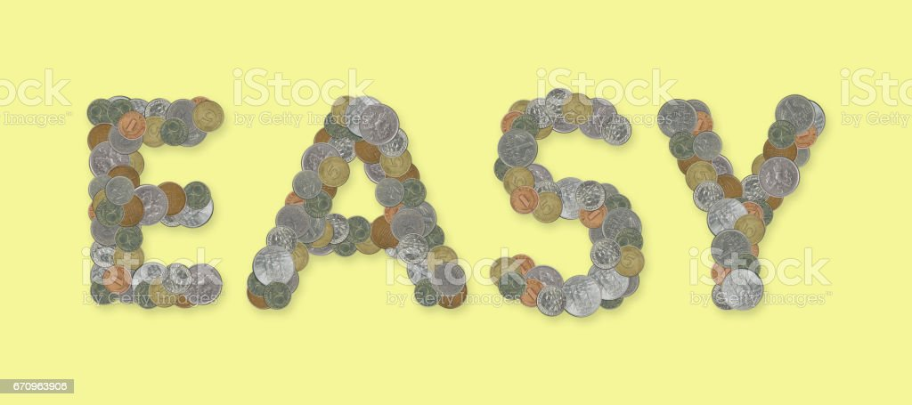 EASY – Coins on yellow background stock photo