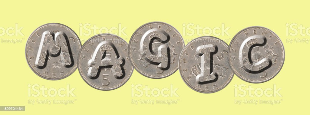 MAGIC – Coins on yellow background stock photo