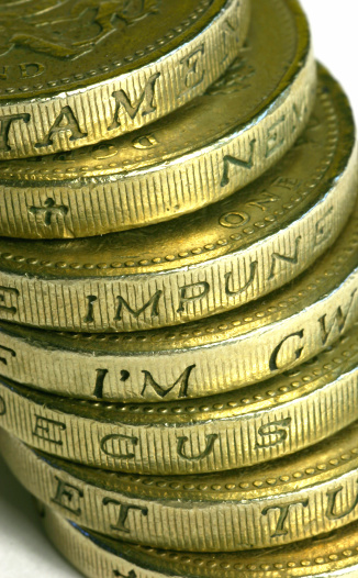 A marco photo of golden coins (UK pounds) with latin words on the sides.