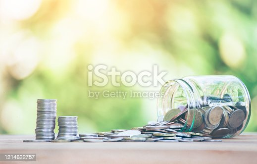 Coins placed  is on table. jar fall down Then there's the coin flowing out go coins, Indicates business growth. planning savings money of coins to buy a home concept property mortgage and investment.