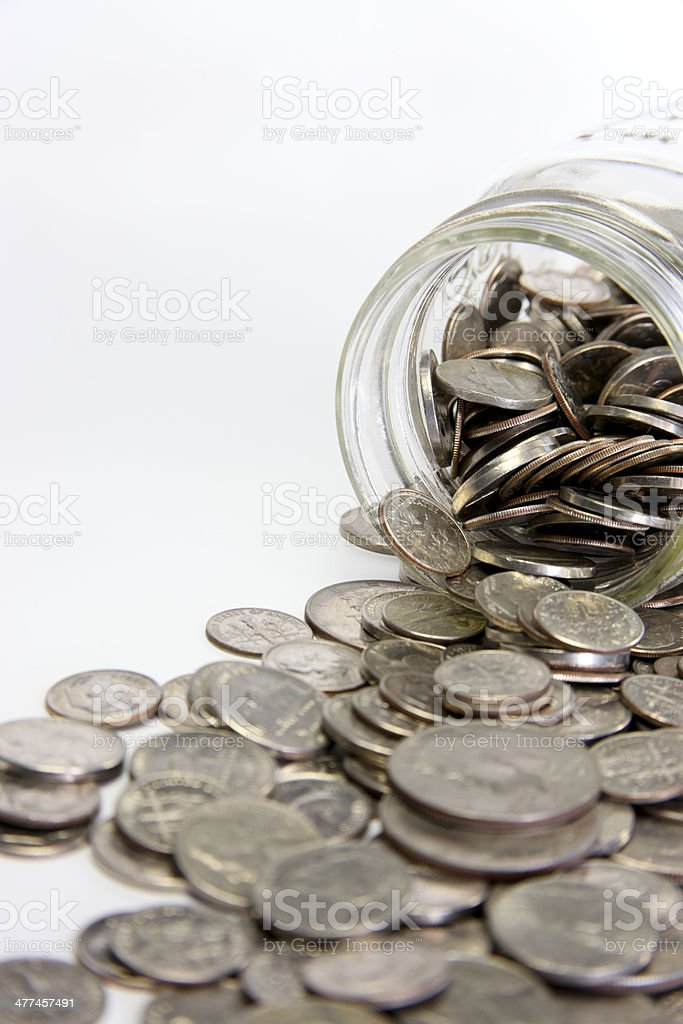Coins Pouring Out of Glass Jar stock photo