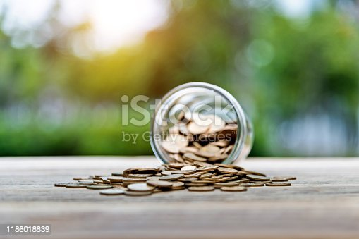 Coins spilling from a glass jar on the table.