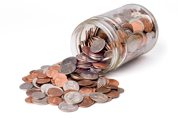 Coins Spilling from a Jar Coins spilling from a jar bank.  Isolated on white with clipping path. dime stock pictures, royalty-free photos & images