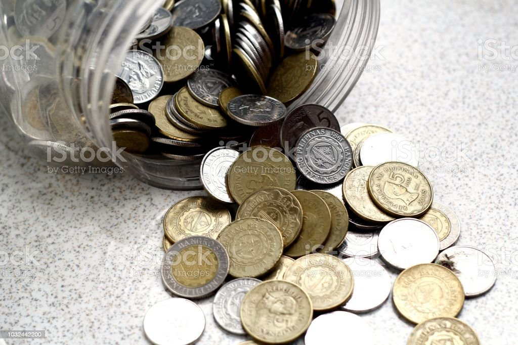 Coins spilling out of a coin bank or container stock photo