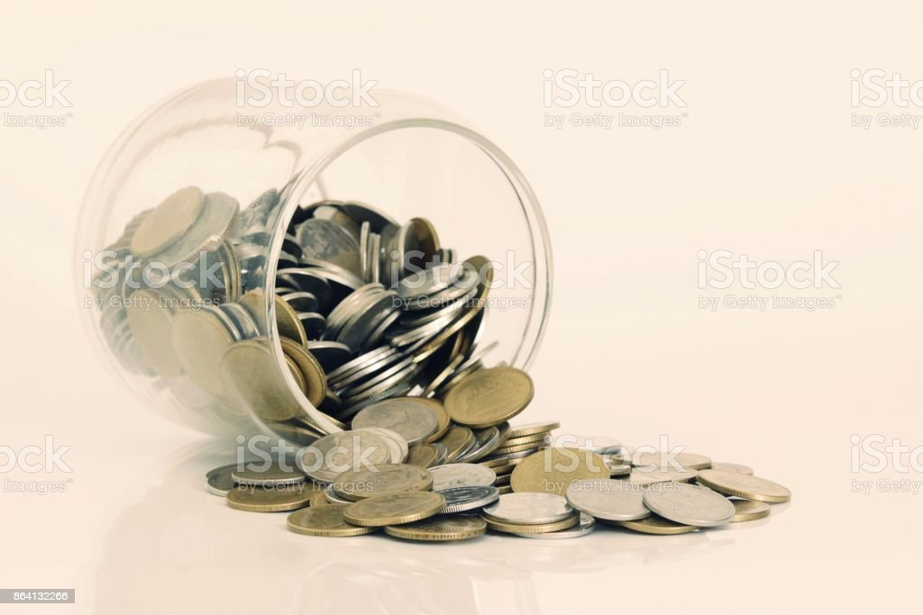 Coins spilling out of a glass bottle royalty-free stock photo