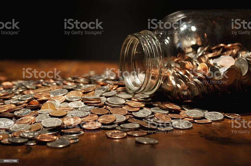 US coins spilling out of large glass jar royalty-free stock photo