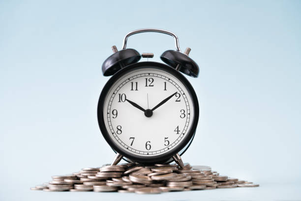 Coins stack and alarm clock on blue background stock photo
