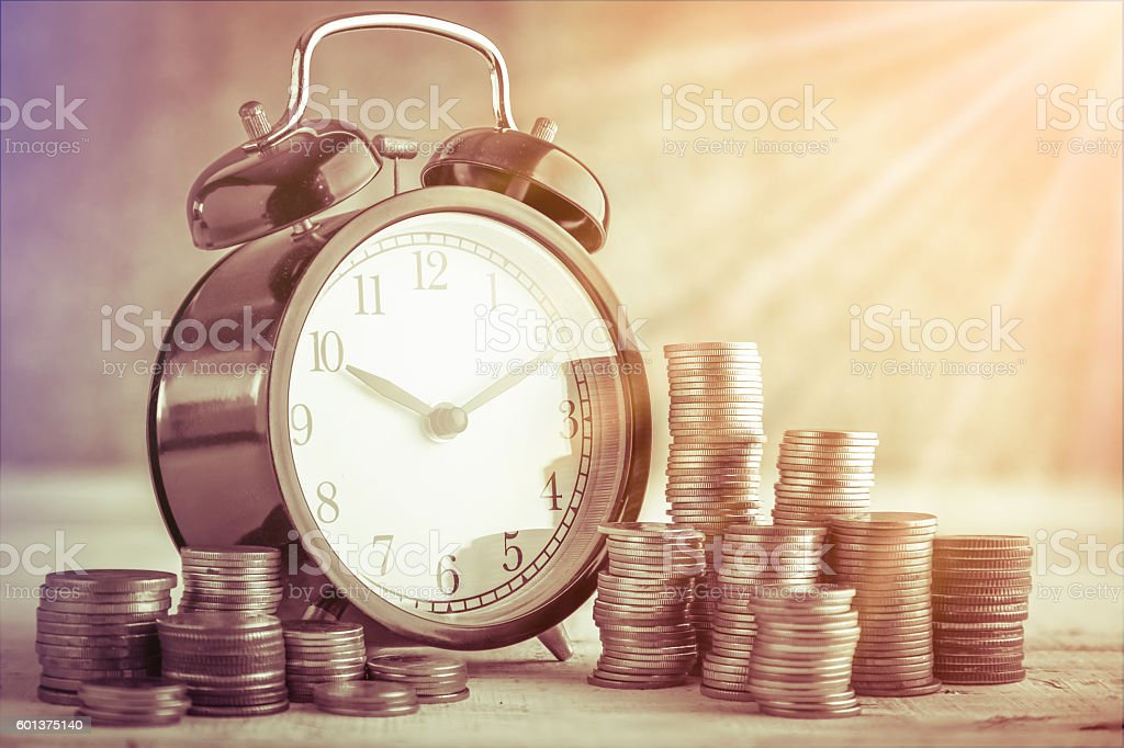 coins stack and alarm clock stock photo