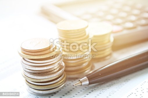 istock Coins stack, calculator, pen and saving account book or financial statement on office desk table 845494014