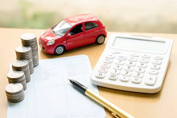 Coins stack in columns on saving book and car stock photo