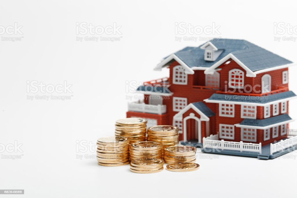 RMB coins stacked in front of the housing model (house prices, house buying, real estate, mortgage concept) stock photo