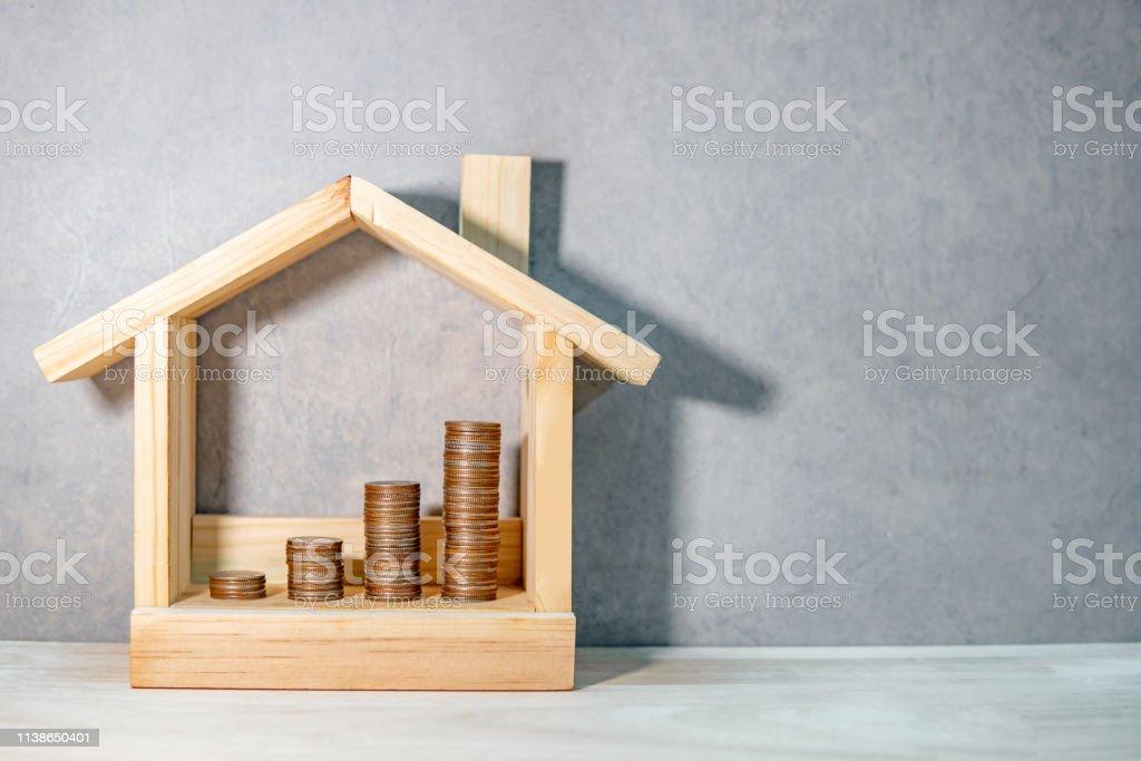 Münzen in Holzhausrahmen auf Tisch gestapelt. Hypothekendarlehen für den Eigenheimhypothekendarlehen. Geld sparen für den künftigen Ruhestand. Immobilieninvestition oder Immobilienleiterkonzept. Wohnprojekt für Baugeschäft - Lizenzfrei Bank Stock-Foto