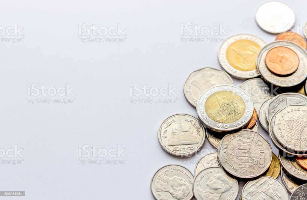 coins tower (Thai money) on white table with over light and soft-focus in the background stock photo