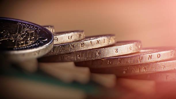2 euro münzen auf dem tisch liegen. münzen auf einem unscharfen hintergrund münze stückelung von zwei euro. - europäische währung stock-fotos und bilder