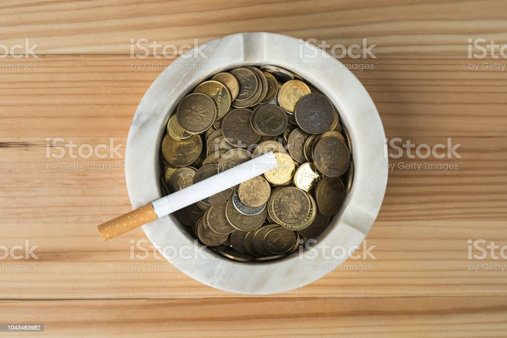 Coins with cigarette in marble ashtray on natural wooden background. stock photo