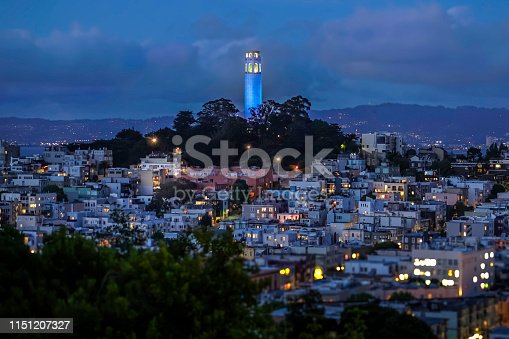 Coit Tower washed in blue light shining above Telegraph Hill. Streetlights and buildings are illuminated in the night sky.