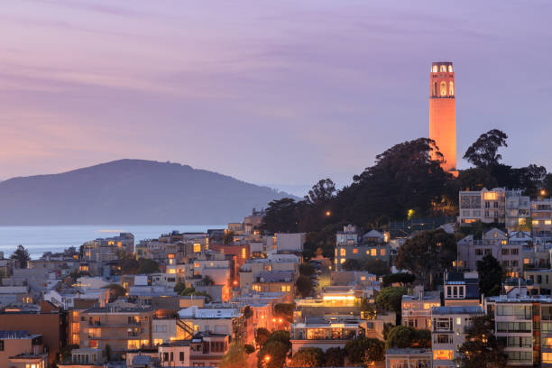 Coit Tower on Telegraph Hill with San Francisco Bay and Angel Island in the background at dusk. stock photo