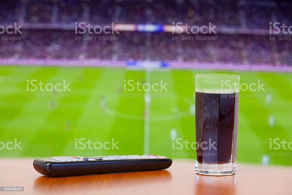 Coke drink, tv remote on a table. Watching soccer. stock photo