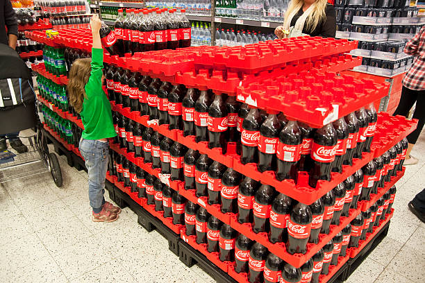 Coca-Cola Åkersberga, Sweden - October, 01th 2011: A little girl picking up a Coca-Cola bottle. The girl is in Willys department store in Åkersberga, Sweden. willys stock pictures, royalty-free photos & images