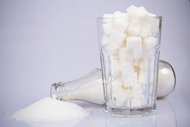 cola-flasche mit zucker und zucker würfel-drei - zuckerfreie lebensmittel stock-fotos und bilder
