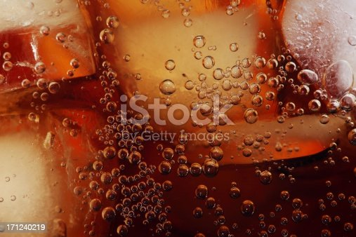 Macro shot of glass with cola drink and ice cubes.