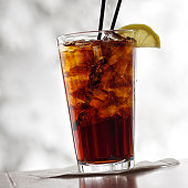 A full glass of cola with ice, straws and slice of lemon. This is inside a room on a table. Also Called Soda or Pop. Looking through a window with a very blurred background of trees and snow.