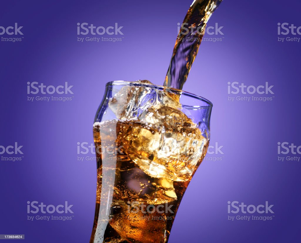 Cola pouring in a glass, isolated on purple stock photo