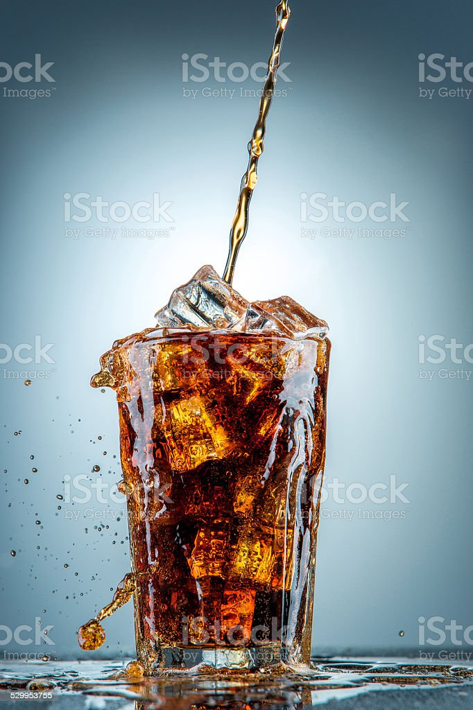 Cola pouring in a glass stock photo