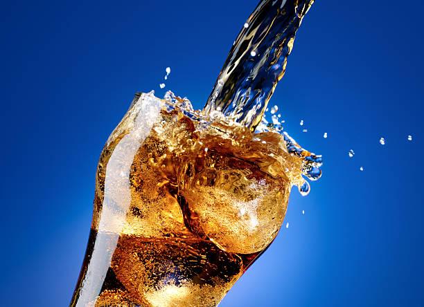 cola mit einem großen spritzer, isoliert auf blau - alkoholfreies getränk stock-fotos und bilder