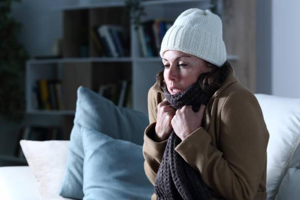 kalte erwachsene frau mit kleidung in der nacht zu hause bedeckt - erkältung und grippe stock-fotos und bilder