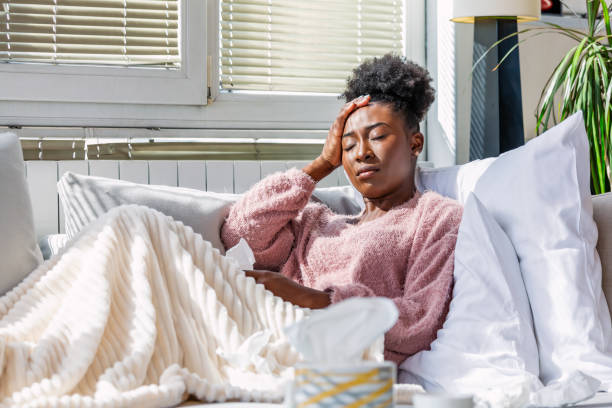 холод и грипп. портрет больной афроамериканки простудился, почувствовав себя больным и чихая в бумажной салфетке. крупным планом красивая � - болезнь стоковые фото и изображения