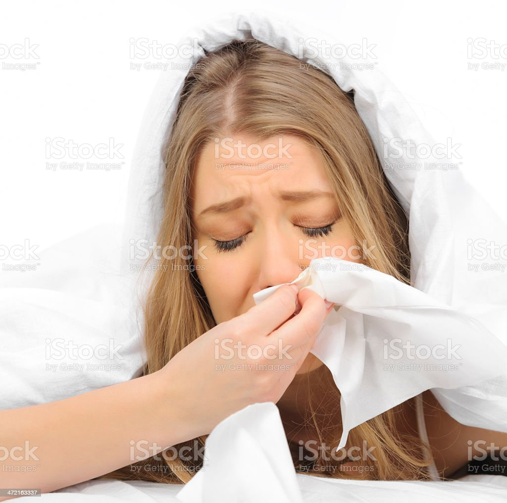crying woman blowing nose feeling unwell.
