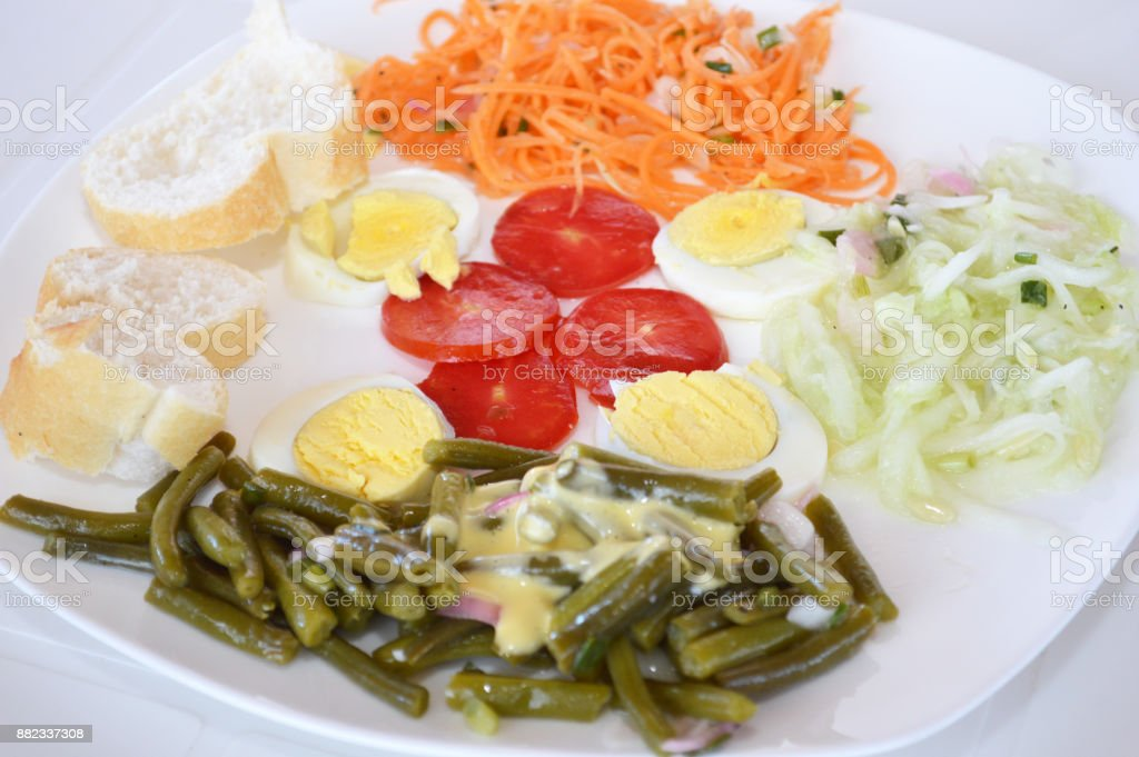 Cold appetizer consisting of slices of French bread, tomato salad, carrot salad, cucumber salad, green bean salad with mayonnaise and hard-boiled egg, sliced in pieces. stock photo