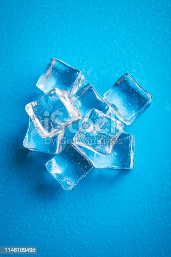 An overhead view of ice cubes on a blue and wet surface.