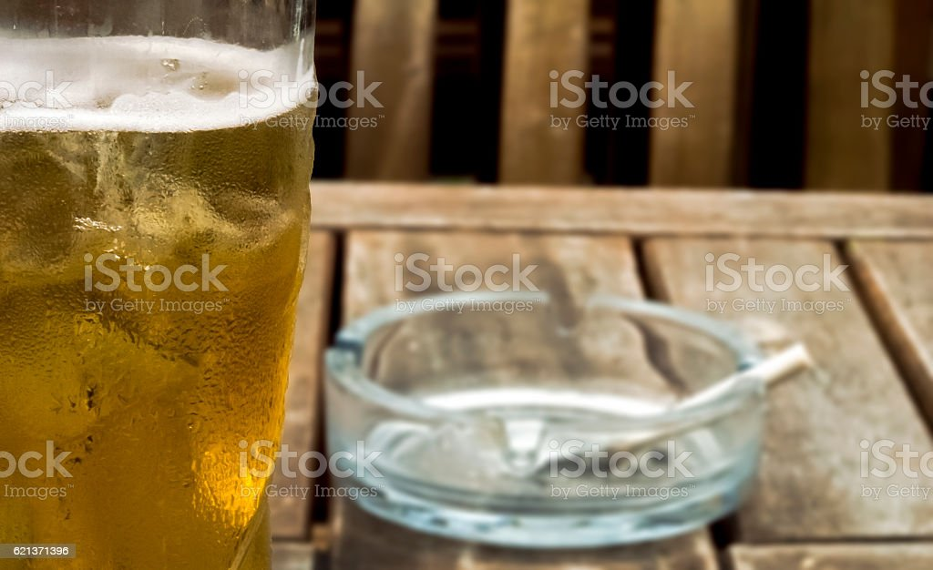 Cold beer and cigarette in ashtray stock photo