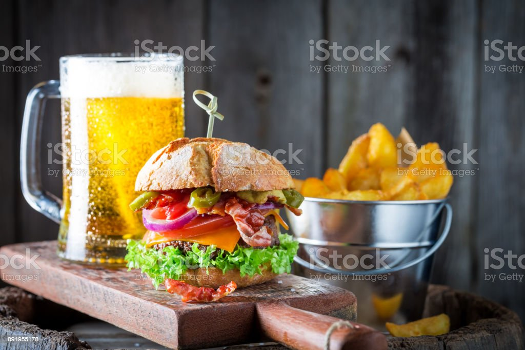Cold beer and hamburger made of beef, cheese and vegetables stock photo