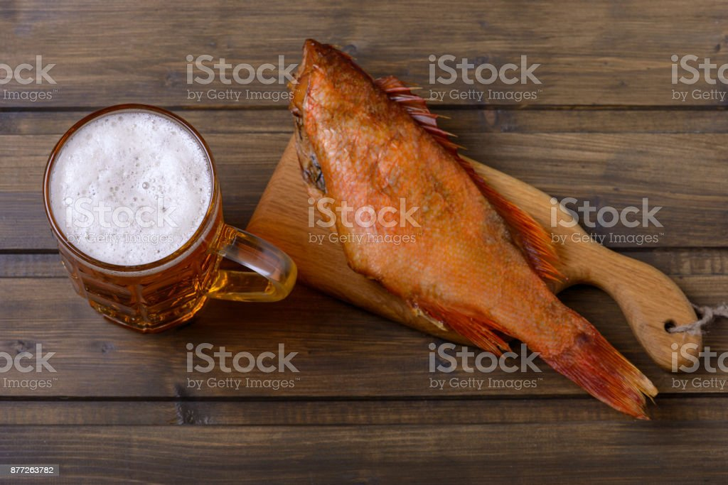 Cold beer and smoked fish on table stock photo