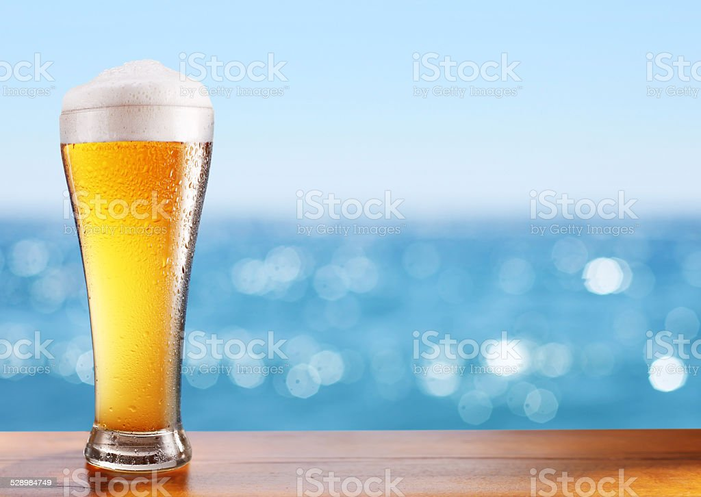 Cold beer glass on the bar table. stock photo
