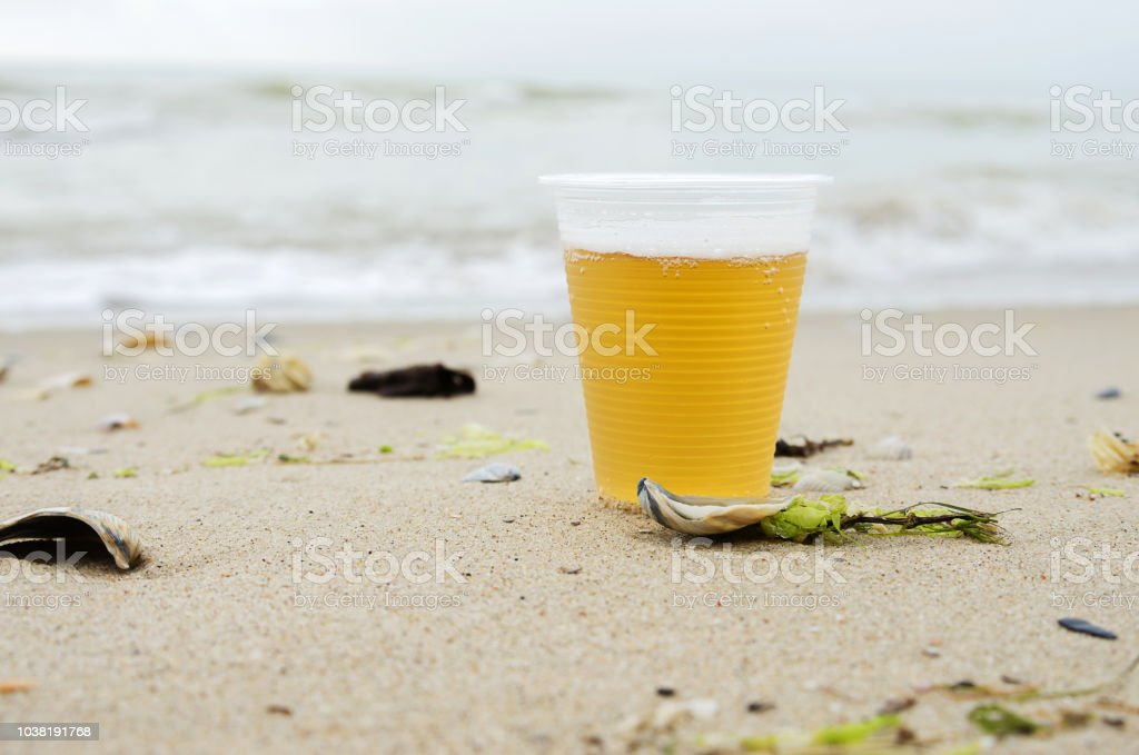 Cold beer in a disposable plastic glass on the beach. Close up,...