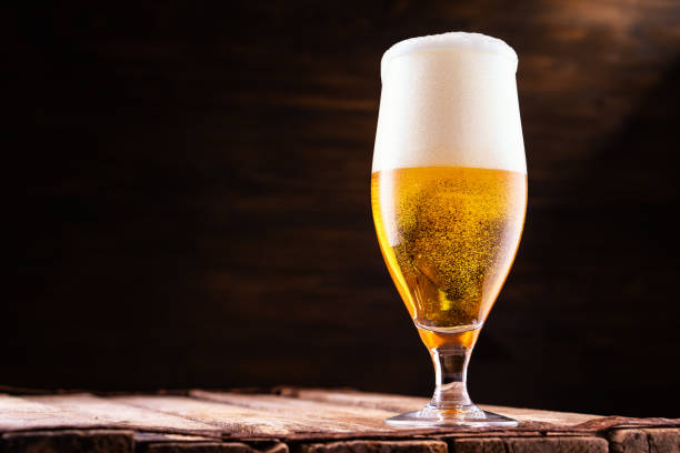 Cold beer into a glass with  foam. stock photo