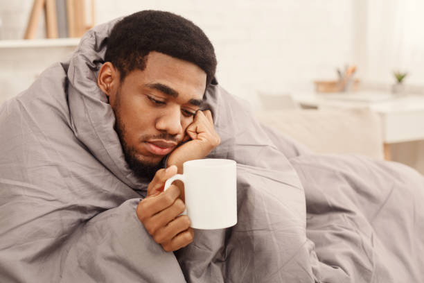 Cold black man with flu wrapped in warm blanket Sad african-american man with flu wrapped in warm blanket, holding cup with tea, copy space wrapped in a blanket stock pictures, royalty-free photos & images